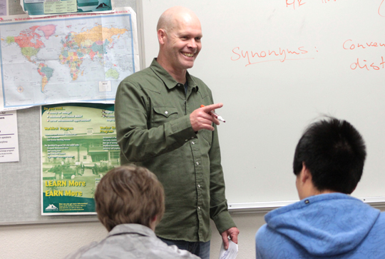 Intensive English instructor stands at white board in from of students