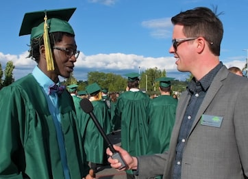 Phil Denman from College Relations interviewing a student before the 2018 commencement ceremony.