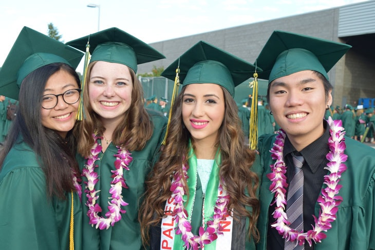 photo of four Green River College students wearing green Green River College graduation caps and gowns.