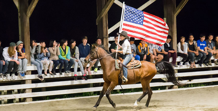 Photo of International students at a Rodeo show at Orientation's overnight camp