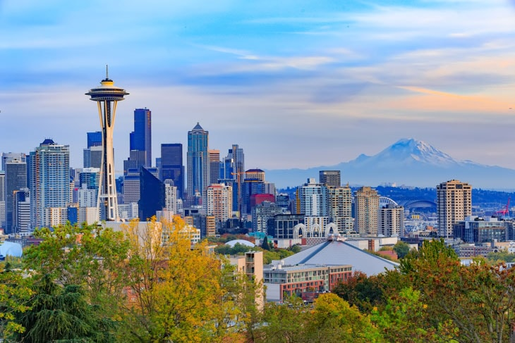 photo showing buildings of the city of Seattle with Mount Rainier in the background