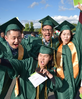 photo of Green River College students in graduation caps and gowns celebrating
