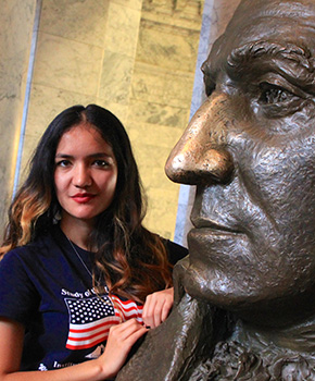 SUSI 2015 participant posing with statue of George Washington at Olympia Capitol Building