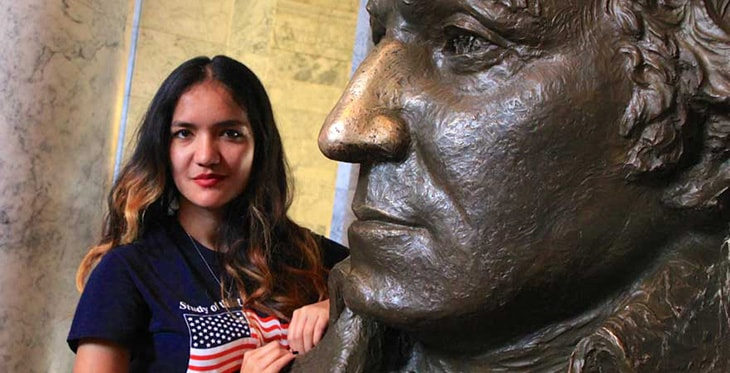 SUSI 2015 participant posing with statue of George Washington at Olympia Capitol Building.