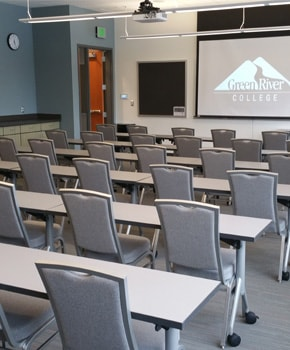 photo of Green River College's Pine Nobel classroom with tables, chairs, and a projector screen