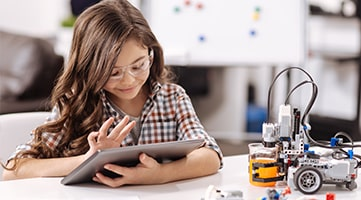 A young girl tapping on a tablet as a small robot sits on the desk next to her.