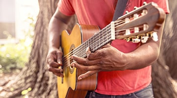 Photo of a man holding and playing a guitar.
