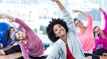 A group of women smiling at the camera as they stretch during a fitness class.