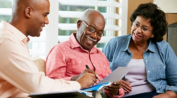 A financial adviser speaking to an elderly couple. They are looking at a document and smiling.