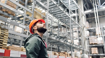 A worker in a warehouse looking up.