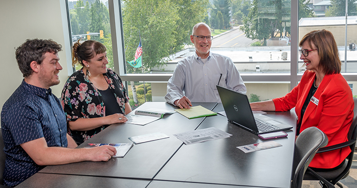 Photo of four individuals sitting at a conference table. Two of the individuals are Small Business Center advisers, and two are Small Business Center clients.