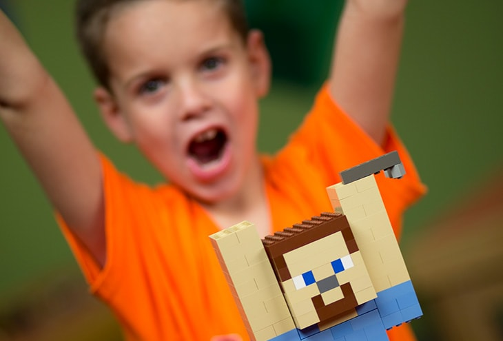 A child with a Minecraft Lego figure.
