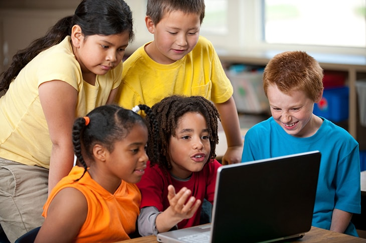 Five children looking at a laptop computer.