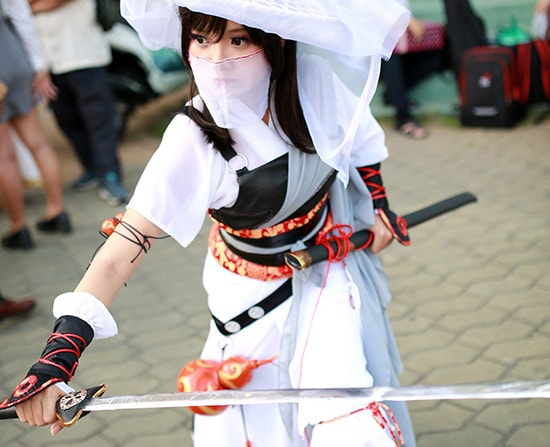 photo of a woman dressed up in a white ninja costume while holding a sword