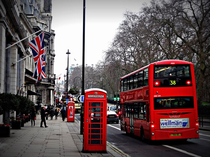 A red telephone booth and double decker bus on a busy street in London.